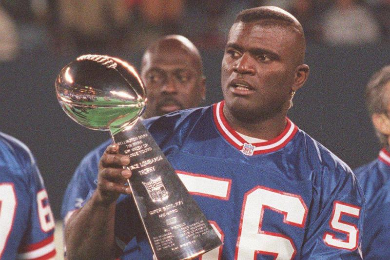 Former New York Giants linebacker Lawrence Taylor holds the Vince Lombardi Trophy at a ceremony honoring the 1986 Super Bowl championship team during half-time of the Dallas Cowboys-Giants football game at Giants Stadium in East Rutherford, New Jersey on November 24, 1996