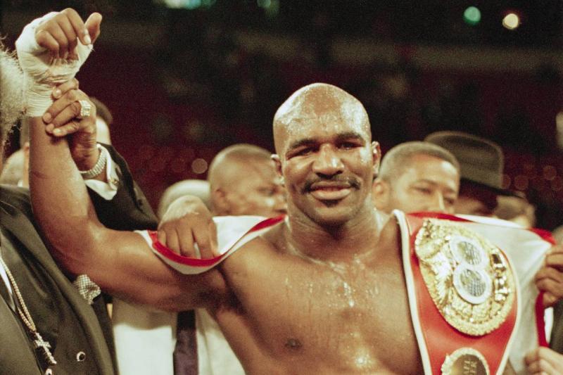 American boxer Evander Holyfield carries his belt after winning the fight against Michael Moorer in Las Vegas, 8th November 1997