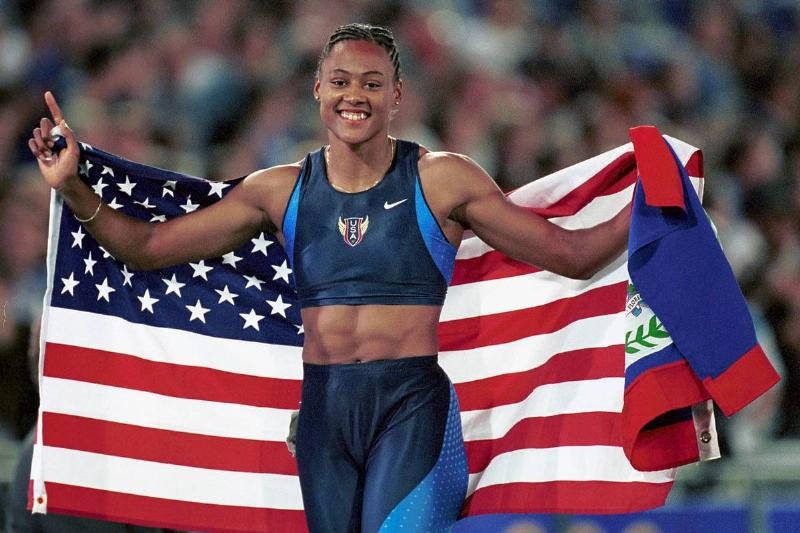 Marion Jones of the USA carries the American flag after winning the Womens 200M gold medal in a time of 21.84 seconds