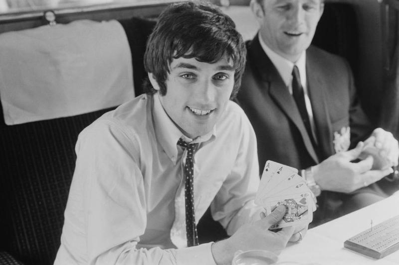 Manchester United FC soccer player George Best (1946 - 2005) plays poker on a train, UK, 27th May 1968